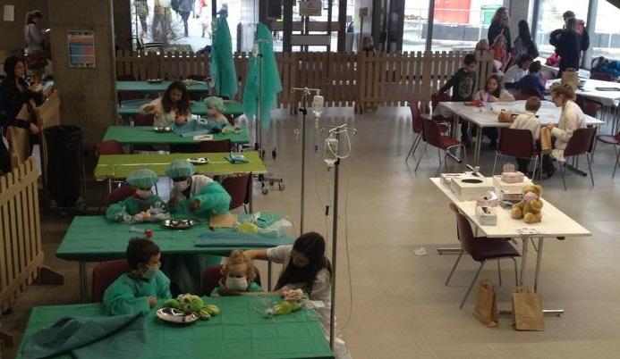 Dans le hall des auditoires, des enfants pratiquent des opérations chirurgicales sur leur peluche