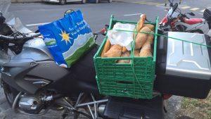 La moto de Chris chargée de nourriture à donner